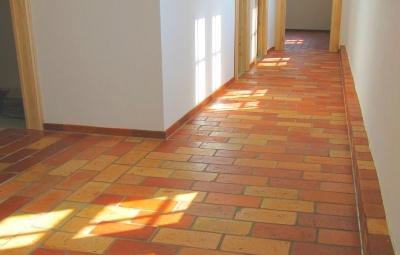 flur-mit-hellen-und-braeunlichen-ziegelfliesen-fussbodenleiste-und-lehmputzwaenden-mittleres-format.jpg