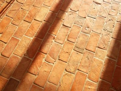 ziegelfussboden-aus-braeunlichen-ziegelfliesen-naturseite-oben-mit-seitlichem-lichteinfall-mittleres-format.jpg